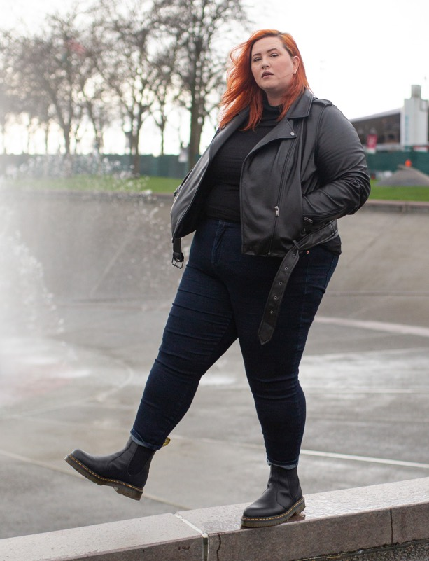 woman wearing leather jacket and dr martens black chelsea boots