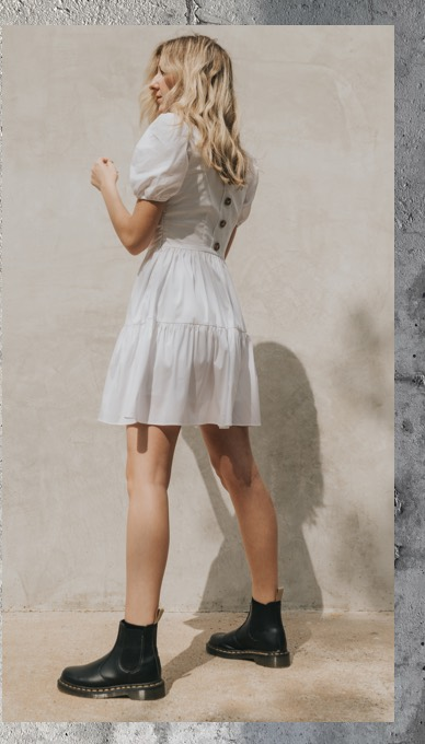 woman wearing black dr martens chelsea boots with white dress