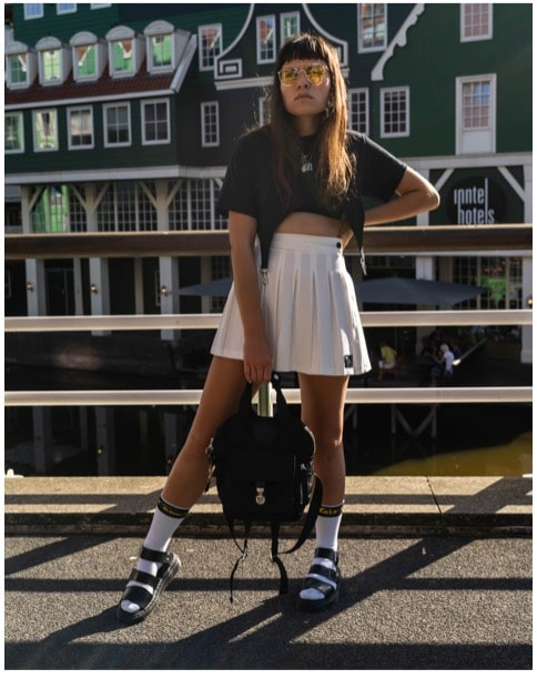 woman styling chunky dr martens sandals with tennis skirt